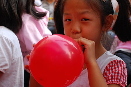 Girl inflating a red balloon